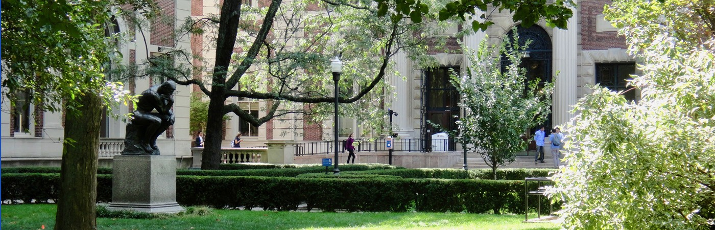 Rodin's The Thinker statue amidst greenery on Columbia University's campus
